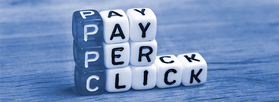 Stacked dice on a table with PPC Pay per Click written