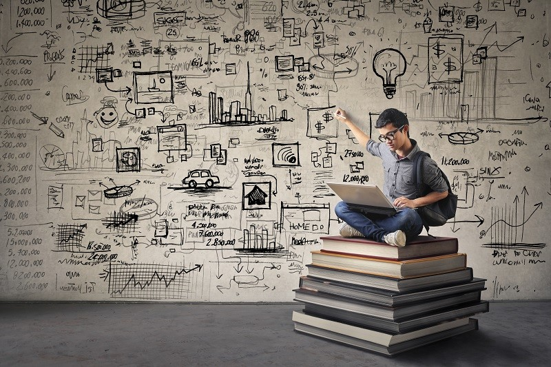 Young boy sitting on some books drawing his ideas on a wall while working on its computer