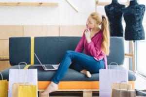 Giovane donna che usa il pc dopo lo shopping