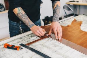 Artigiano calzolaio che taglia la pelle sopra un tavolo di lavoro