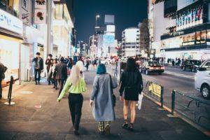 Tre ragazze di spalle che camminano in una metropoli